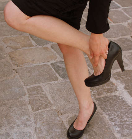 foot pain: Business woman with tired and sore feet