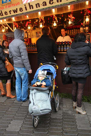 christkindlesmarkt: NUREMBERG, GERMANY - DECEMBER 23, 2013: A child in a fun hat sitting in a pram and waiting for parents near the Gluhwein stall at the Christmas fair in Nuremberg, Germany