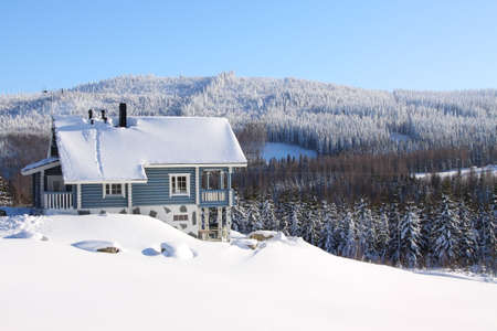 two storey house: Log house in the snow in the sunhine Stock Photo