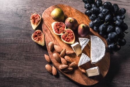 Cheese plate served with grapes, figs and nuts on a wooden background. Close - up.