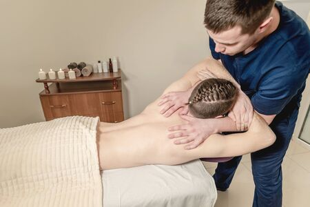 Masseur makes massage to the patient. Massage in a medical institution. Imagens