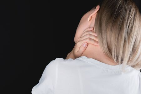 The girl clings to her neck in pain. Close-up of arms and neck from the back. Isolated black background.