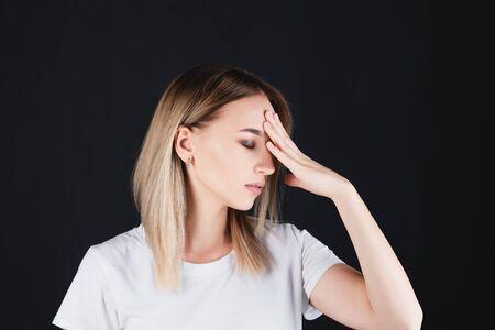 Portrait d'une fille qui s'accroche à la tête avec des mains douloureuses. Banque d'images