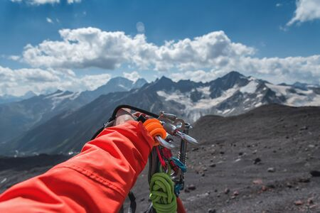 First-person view of a hand with climbing equipment high in the mountains. Mountain climbing. Banque d'images