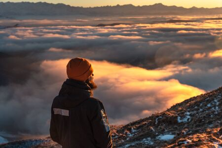 A man stands high in the mountains, at sunset, above the clouds.