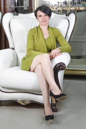 Portrait of a nice adult woman sitting in a beautiful expensive chair
