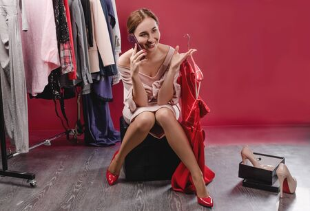 Beautiful girl choosing clothes speaks on the phone Stock fotó