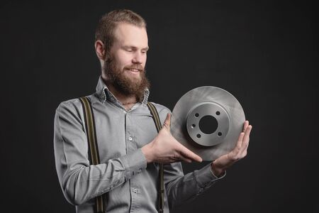 Handsome young man presents car parts on a gray background. The concept of sales and testing of goods 版權商用圖片
