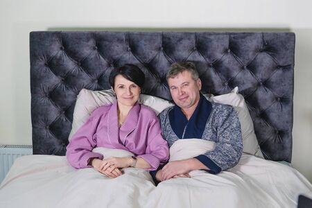 Adult married couple sitting on the bed in the bedroom. Family relationships. The concept of family life, relaxation and pastime.