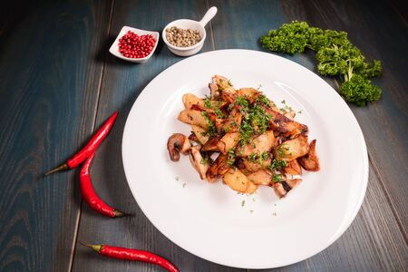A plate of appetizing potato with mushrooms on a wooden table, among seasonings. Studio photography of food in the cooking industry, dark background.
