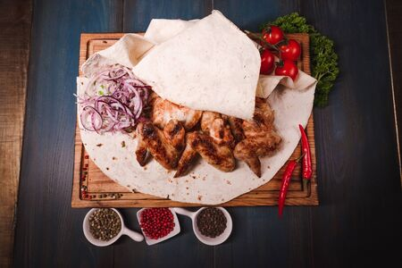 Appetizing fried chicken wings on a wooden tray. Studio photography of food in the cooking industry, dark background