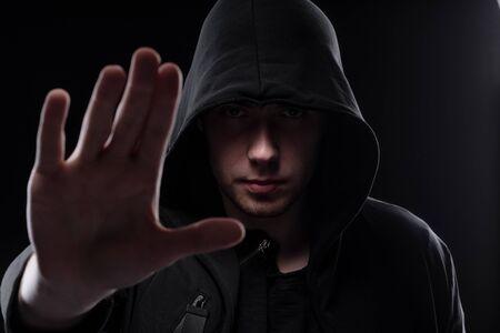 Un homme dans une cagoule noire sur fond noir, photographie de studio. L'idée de mysticisme, de mystère, de crime et de tromperie