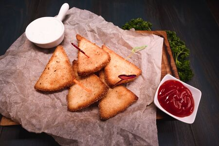Appetizing fried cheese with sauce on a wooden tray. Studio photography of food in the cooking industry, dark background