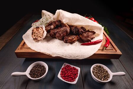 Appetizing fried meat lies on a wooden tray, among the seasonings. Studio photography of food in the cooking industry, dark background