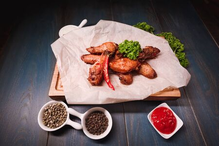 Appetizing fried chicken wings on a wooden tray. Studio photography of food in the cooking industry, dark background.
