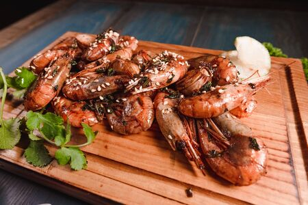 Appetizing fried prawns on a wooden tray among seasonings. Studio photography of food in the cooking industry, dark background