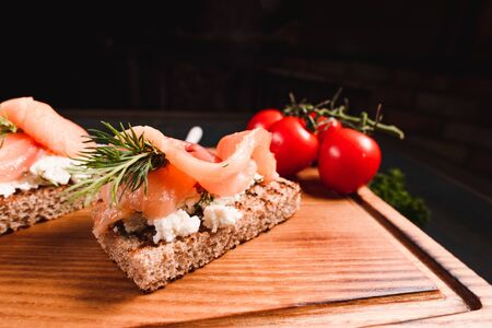 Sandwiches with red fish and cheese on a wooden board on a dark background. Studio photography of food in the cooking industry, dark background.