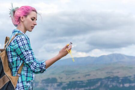 A beautiful girl stands high in the beautiful mountains with a compass in her hands. The concept of navigating the search for your own path and orientation to the cardinal points