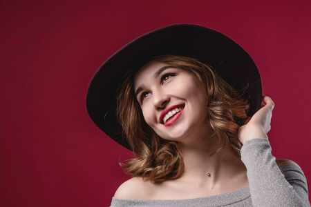 Portrait of a beautiful girl who straightens a hat on a red background. The concept of beauty and youth