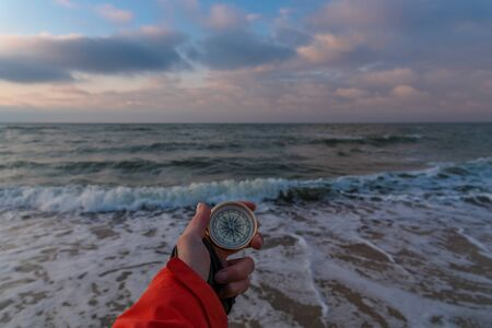 First-person view of a female hand with a compass on a background of a beautiful sea landscape. The concept of navigating the search for your own path and orientation to the cardinal points