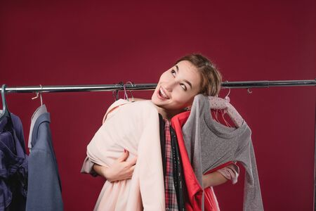 Beautiful girl chooses and tries on clothes on a red background. The concept of choosing and buying clothes, shopaholism and consumerism