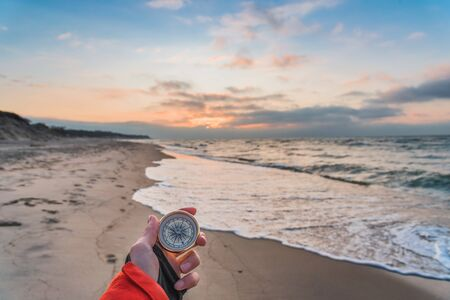 First-person view of a female hand with a compass on a background of a beautiful sea landscape. The concept of navigating the search for your own path and orientation to the cardinal points.