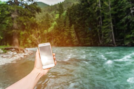 First-person view of a female hand with a phone on a background of a beautiful river and forest in the mountains in summer. Communication concept on vacation and tourism. Фото со стока