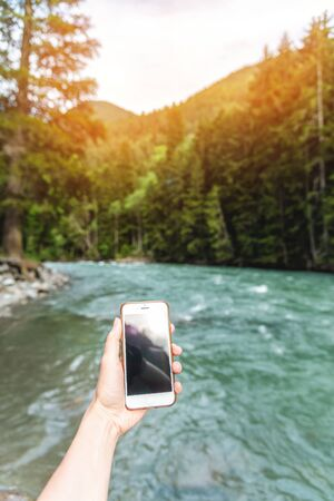 First-person view of a female hand with a phone on a background of a beautiful river and forest in the mountains in summer. Communication concept on vacation and tourism. Stok Fotoğraf
