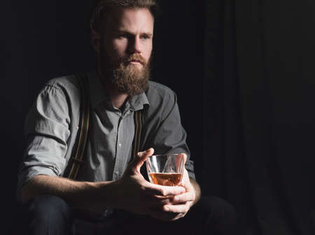 A handsome young man with a beard is sitting in a dark room with a glass of alcohol in his hands. The concept of rest and relaxation, booze and loneliness