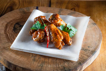 Appetizing fried chicken wings in sauce on a wooden tray. The concept of food and serving, food in bars and restaurants.
