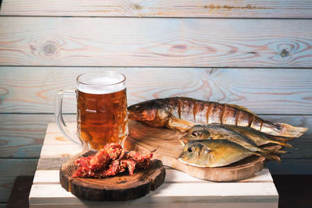 Mug with beer and snacks on a background of a brick wall on the table. The concept of relaxation, bars and parties. Reklamní fotografie