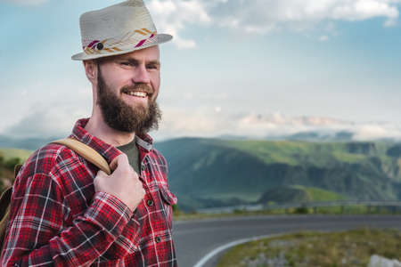 Handsome young man in a straw hat and a plaid shirt, stands on the road, against the backdrop of beautiful mountains. The concept of freedom and hitchhiking