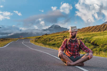 Handsome young man, in a plaid shirt and shorts, sits on a track in the mountains at sunset. Freedom and travel hitchhiking concept