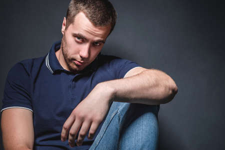 Young attractive man in blue jeans and a polo shirt sits on the floor near the wall in the studio. Youth and attractiveness concept
