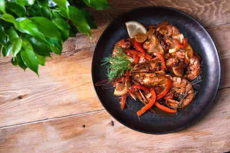 Delicious fried langoustines in sauce on a black plate, prepared in an Asian style. Fast and ready meal concept