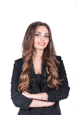 A beautiful woman in a black business suit with a make-up and long hair stands on a white isolated background in the studio. Working and business woman concept Stok Fotoğraf