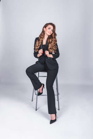 A beautiful woman in a black business suit with a make-up and long hair sits on a high chair on a white background in the studio. Working and business woman concept