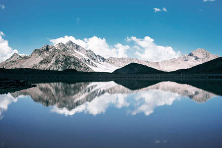 Beautiful landscape of snow-capped mountains and reflections in the lake. The concept of mountain climbing and extreme recreation