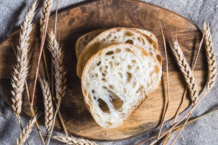 A loaf of traditional ciabatta on a wooden tray on the table. Craft bread concept