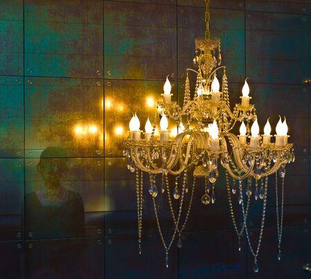 Crystal chandelier lighting near the mirror wall photo