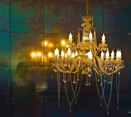 Crystal chandelier lighting near the mirror wall Stock Photo