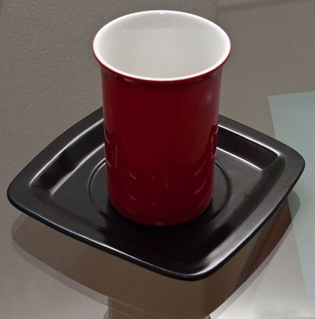vivacity: Red cup on the black plate Stock Photo