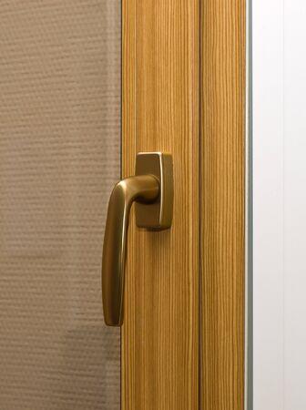 Window handle on fiberglass window. Gold color. photo