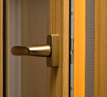 Window handle on fiberglass window. Gold color. photo