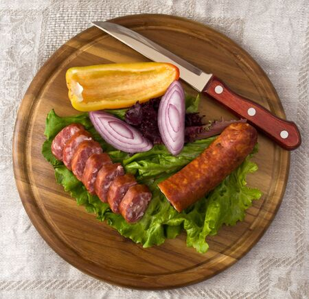 Breakfast close-up. Slices of sausage on the wooden plate with knife Stockfoto