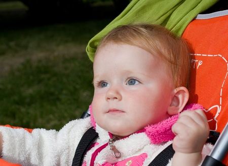 1 year old girl sitting in baby carriage photo