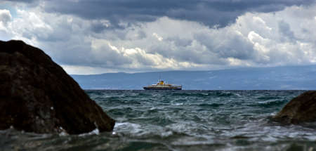 Small vessel in a stormy weather sea photo