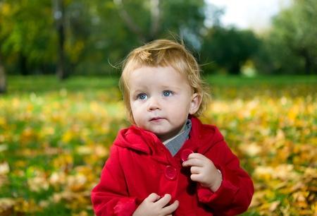 Cute little blonde girl in autumn park photo