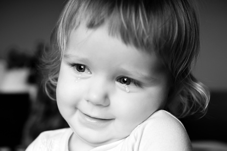 Crying little girl with focus on her tears photo