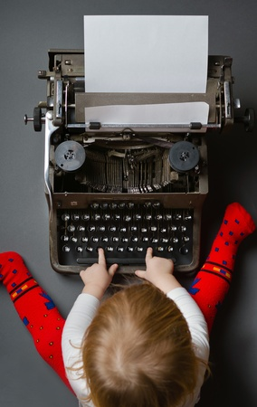 Cute little baby typing on retro typewriter photo